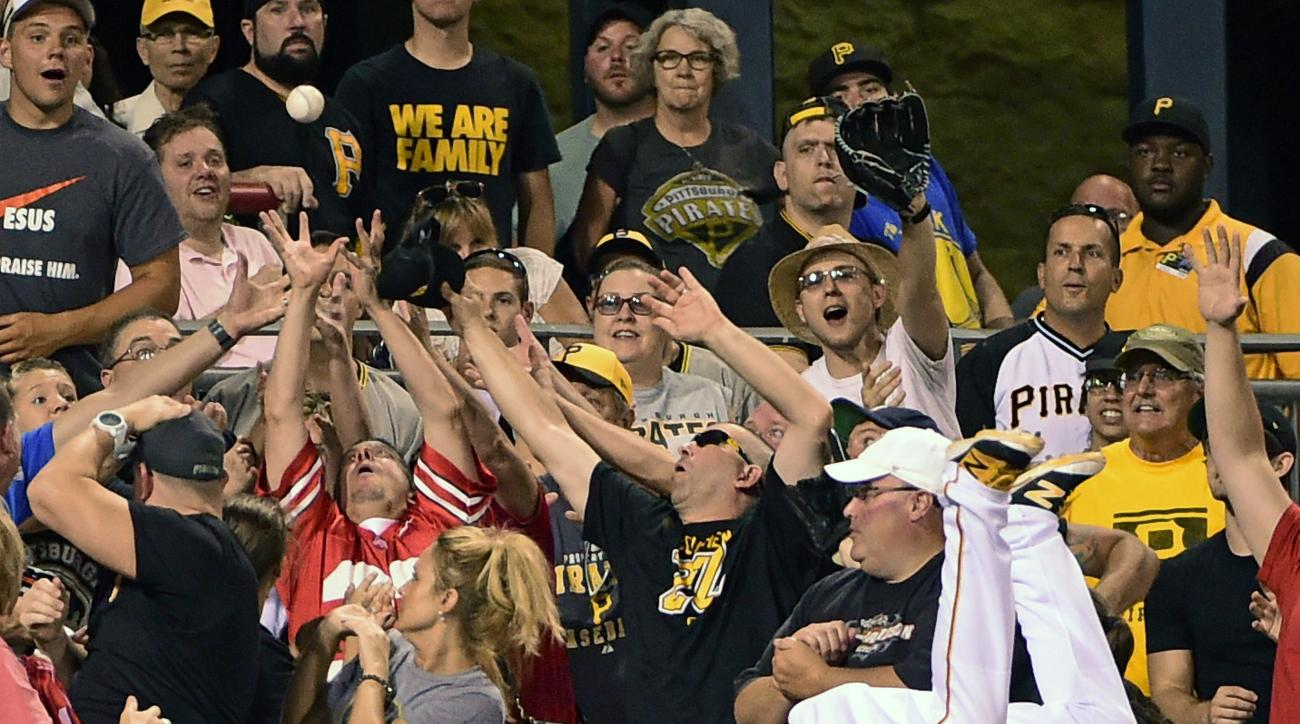 Fans reach for Cincinnati Reds Brandon Phillips's home run ball as Pittsburgh Pirates left fielder Starling Marte, tries in vain to make a catch in the seventh inning of a baseball game in Pittsburgh, Saturday, Aug. 6, 2016. (AP Photo/Fred Vuich)