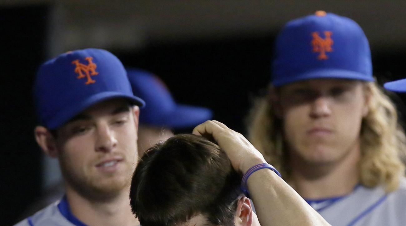 New York Mets' Neil Walker (20) rubs the back of his head after getting hit with a ball thrown by Detroit Tigers' Miguel Cabrera towards second base in an attempt to start a double play during the seventh inning of an interleague baseball game Saturday, A