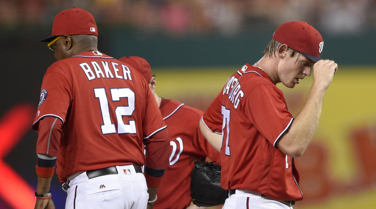 Washington Nationals starting pitcher Stephen Strasburg, right, walks towards the dugout after he was pulled from the game by manager Dusty Baker (12) during the fifth inning of a baseball game against the San Francisco Giants, Saturday, Aug. 6, 2016, in