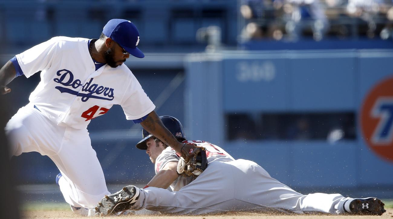 Boston Red Sox's Andrew Benintendi, right, steals second as Los Angeles Dodgers second baseman Howie Kendrick, left, applies the late tag during the third inning of a baseball game in Los Angeles, Sunday, Aug. 7, 2016. (AP Photo/Alex Gallardo)