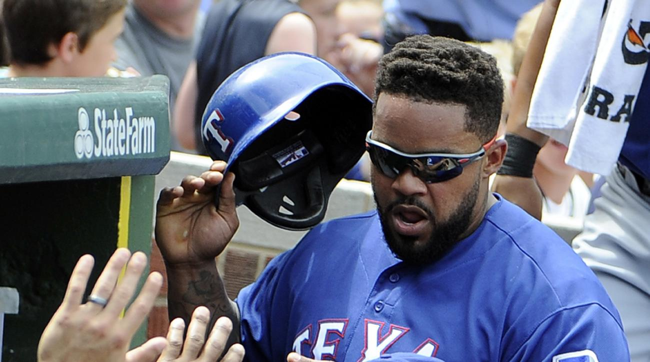 FILE - In this July 17, 2016, file photo, Texas Rangers' Prince Fielder is greeted after scoring against the Chicago Cubs during a baseball game in Chicago. A person with direct knowledge of the medical decision says Fielder will have to quit playing base