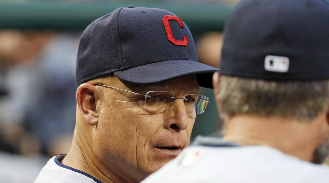 Cleveland Indians bench coach Brad Mills, left, talks with assistant hitting coach Matt Quatraro during the third inning of a baseball game against the Washington Nationals at Nationals Park, Tuesday, Aug. 9, 2016, in Washington. (AP Photo/Alex Brandon)