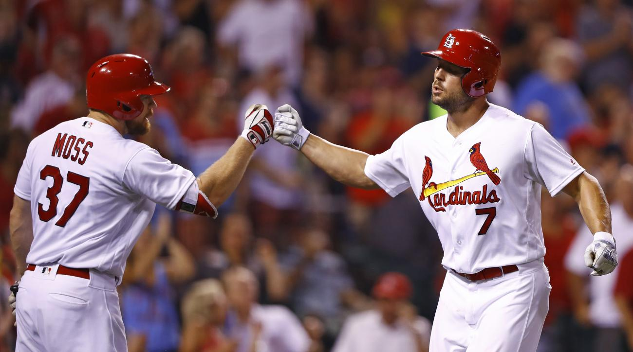 St. Louis Cardinals' Matt Holliday, right, is congratulated by Brandon Moss after hitting a home run off of Cincinnati Reds starting pitcher Brandon Finnegan during the fifth inning of a baseball game, Tuesday, Aug. 9, 2016, in St. Louis. (AP Photo/Billy