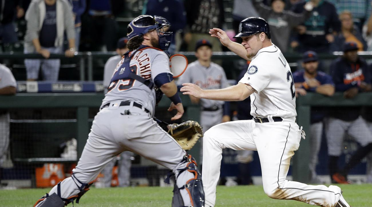Seattle Mariners' Adam Lind, right, scores the winning run as Detroit Tigers catcher Jarrod Saltalamacchia waits for the throw in the 15th inning of a baseball game Wednesday, Aug. 10, 2016, in Seattle. The Mariners won 6-5. (AP Photo/Elaine Thompson)