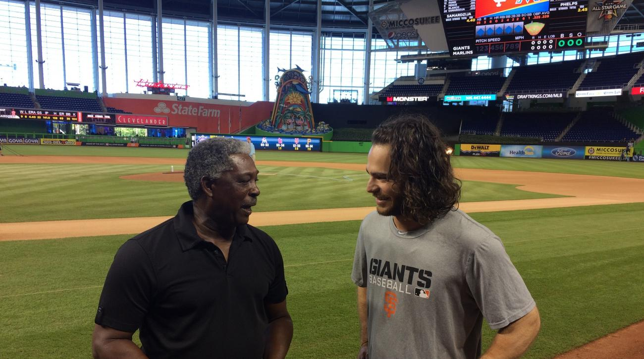 Rennie Stennett, left, and San Francisco Giants' Brandon Crawford chat about the NL record they share before the start of a baseball game, Wednesday, Aug. 10, 2016, in Miami. Crawford tied the record with seven hits in Monday's 14-inning victory in Miami,