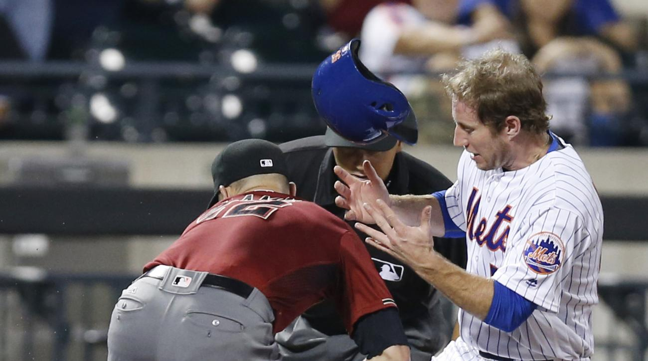 Third base umpire Vic Carapazza, center, watches as Arizona Diamondbacks third baseman Jake Lamb, left, tries to tag New York Mets' Ty Kelly, who advanced on a passed ball during the fourth inning of a baseball game, Wednesday, Aug. 10, 2016, in New York.