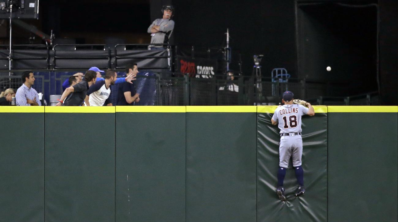 Detroit Tigers center fielder Tyler Collins and fans watch the home-run ball of Seattle Mariners' Nelson Cruz go over the outfield wall during the eighth inning of a baseball game Wednesday, Aug. 10, 2016, in Seattle. (AP Photo/Elaine Thompson)