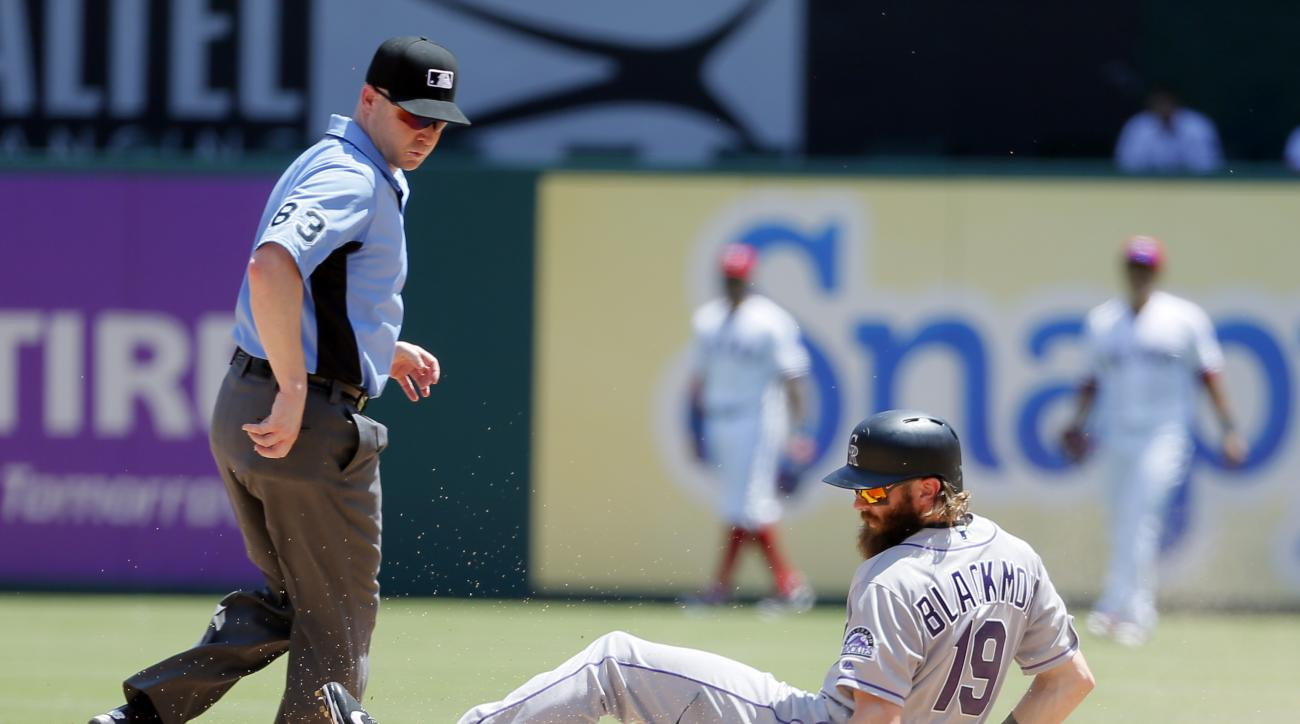 Second base umpire Mike Estabrook watches as Colorado Rockies' Charlie Blackmon slides into second for a double against the Texas Rangers in the fourth inning of a baseball game, Thursday, Aug. 11, 2016, in Arlington, Texas. (AP Photo/Tony Gutierrez)