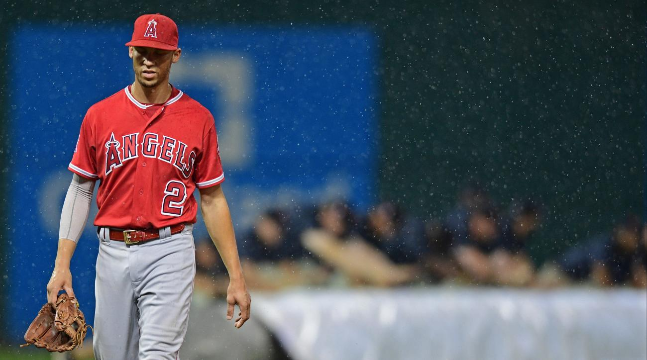 Los Angeles Angels' Andrelton Simmons returns to the dugout as grounds crew workers push the tarp onto the field in the fourth inning of the Angels' baseball game against the Cleveland Indians, Thursday, Aug. 11, 2016, in Cleveland. (AP Photo/David Dermer