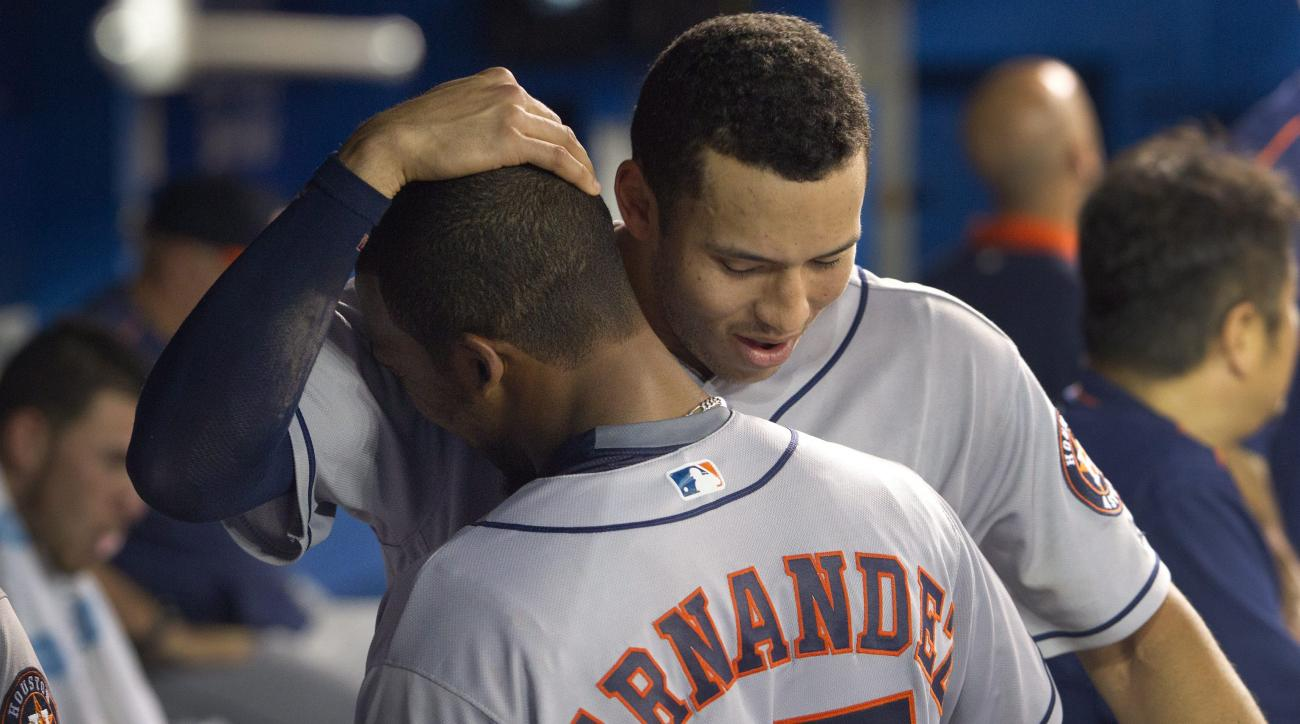 Houston Astros Teoscar Hernandez, left, gets a hug from teammate Carlos Correa after he got his first major league hit, a home run, against the Toronto Blue Jays in the sixth inning of a baseball game in Toronto, Friday, Aug. 12, 2016. (Fred Thornhill/The