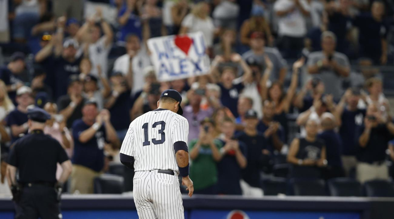 Fans applaud and hold signs as New York Yankees Alex Rodriguez (13) takes his position at third base in the ninth inning of his final game as a Yankee player, against the Tampa Bay Rays at Yankee Stadium in New York, Friday, Aug. 12, 2016. The Yankees won