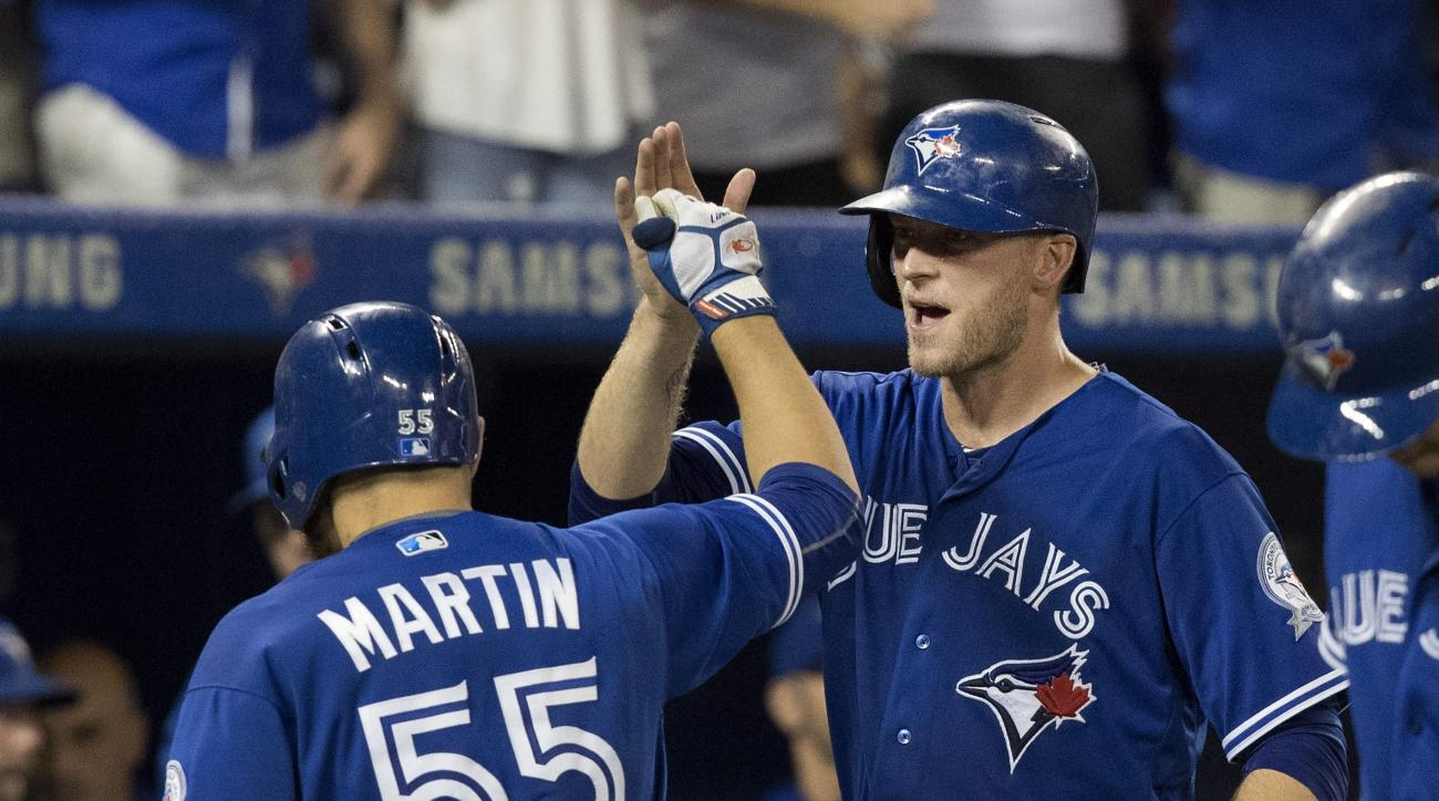 Toronto Blue Jays' Russell Martin high-fives with teammate Michael Saunders after hitting a three-run home run against the Houston Astros in the sixth inning of a baseball game in Toronto, Saturday, Aug. 13, 2016. (Fred Thornhill/The Canadian Press via AP