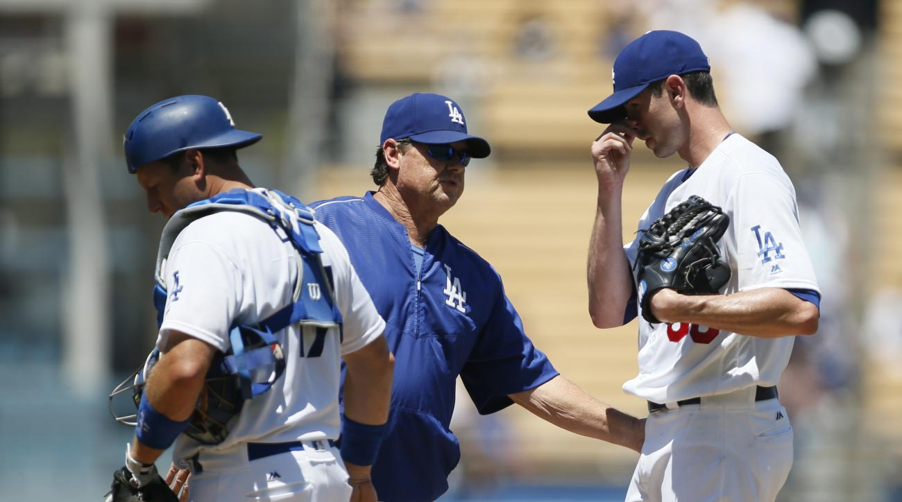 Los Angeles Dodgers starting pitcher Brandon McCarthy, right, gets a visit to the mound by pitching coach Rick Honeycutt, center, and catcher A.J. Ellis, left, after walking Pittsburgh Pirates' John Jaso with the bases loaded to allow Starling Marte to sc