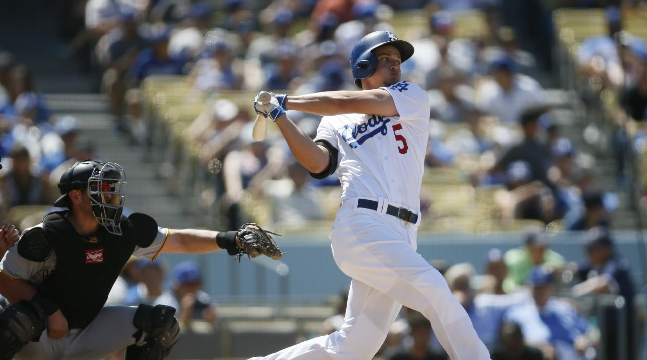 Los Angeles Dodgers shortstop Corey Seager hits an RBI single in front of Pittsburgh Pirates catcher Francisco Cervelli, left, during the fourth inning of a baseball game, Saturday, Aug. 13, 2016, in Los Angeles. (AP Photo/Danny Moloshok)
