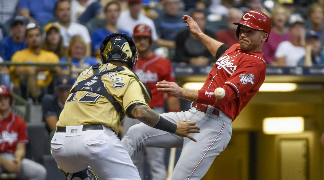 Cincinnati Reds' Joey Votto, right, scores as the ball gets by Milwaukee Brewers catcher Martin Maldonado, left, during the sixth inning of a baseball game Saturday, Aug. 13, 2016, in Milwaukee. (AP Photo/Benny Sieu)