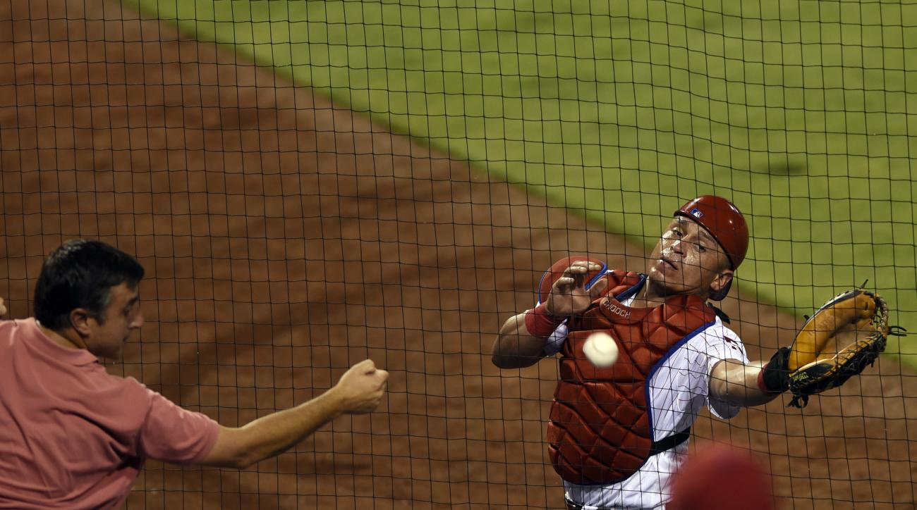 Philadelphia Phillies catcher Carlos Ruiz reaches for a ball that went behind the home plate net hit by Colorado Rockies' Ben Paulsen in the sixth inning of a baseball game on Saturday, Aug. 13, 2016, in Philadelphia. The Phillies beat the Rockies 6-3. (A