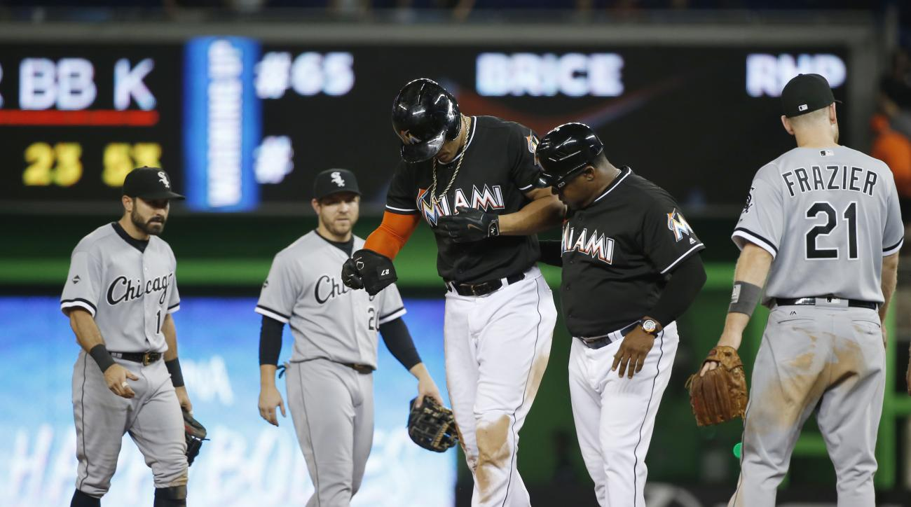 Miami Marlins' Giancarlo Stanton, center, is helped off the field by third base coach Lenny Harris after Stanton was put out as he attempted to reach second base during the ninth inning of a baseball game against the Chicago White Sox, Saturday, Aug. 13,