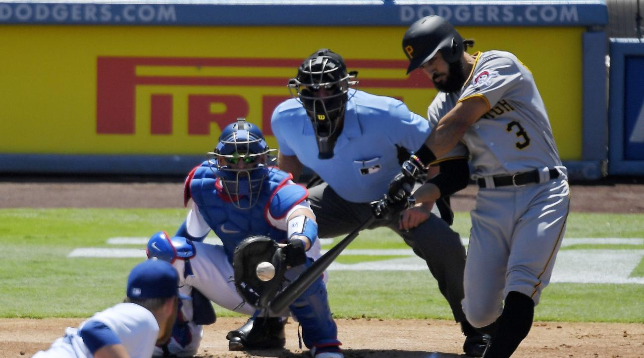 Pittsburgh Pirates' Sean Rodriguez, right, hits a three-run home run while Los Angeles Dodgers starting pitcher Brett Anderson, lower left, watches along with catcher Yasmani Grandal, upper left, and home plate umpire Chad Fairchild, upper center, during