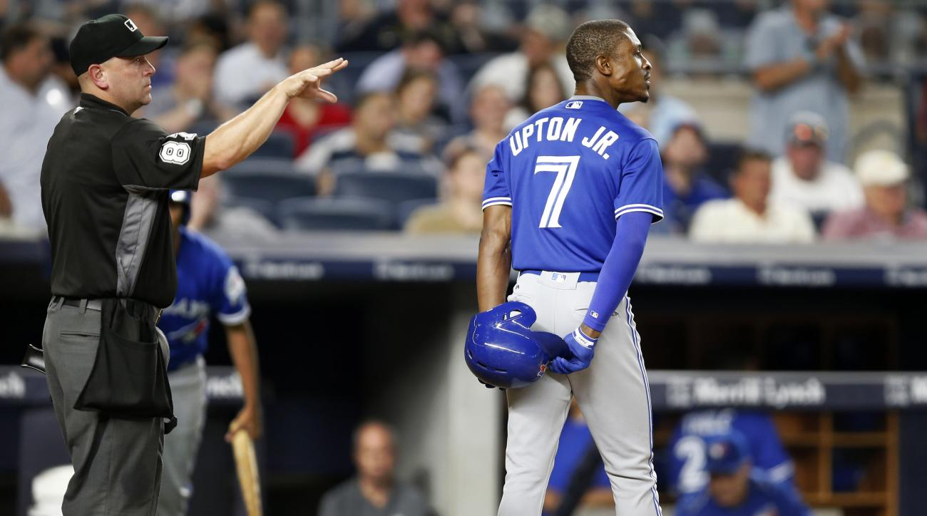 Home plate umpire Scott Barry (87) who came in for Hunter Wendelstadt after Wendelstadt left the game, signals to the pitcher after Toronto Blue Jays' Melvin Upton Jr. (7) reacts to striking out looking in a baseball game against the New York Yankees in N
