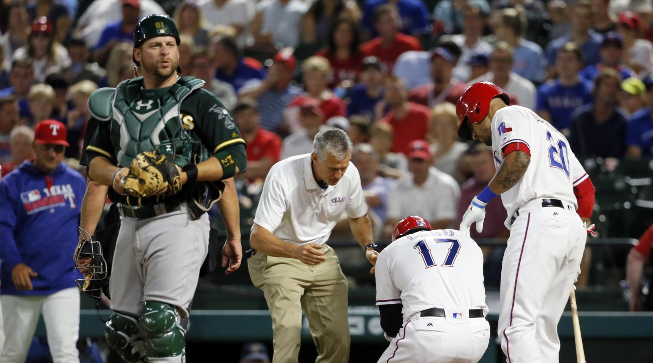 Oakland Athletics catcher Stephen Vogt walks away from the plate as Texas Rangers athletic trainer Kevin Harmon, center, and Ian Desmond (20) check on Shin-Soo Choo (17) of South Korea, who was hit on the left wrist by a pitch from Oakland Athletics' Ross