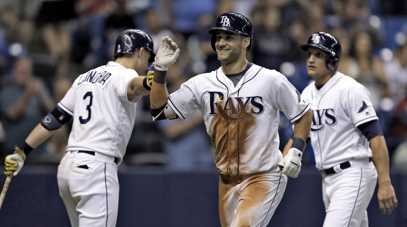 Tampa Bay Rays' Kevin Kiermaier, center, celebrates with Evan Longoria, left, and Mikie Mahtook, right, after his three-run home run off San Diego Padres relief pitcher Leonel Campos during the eighth inning of an interleague baseball game, Monday, Aug. 1