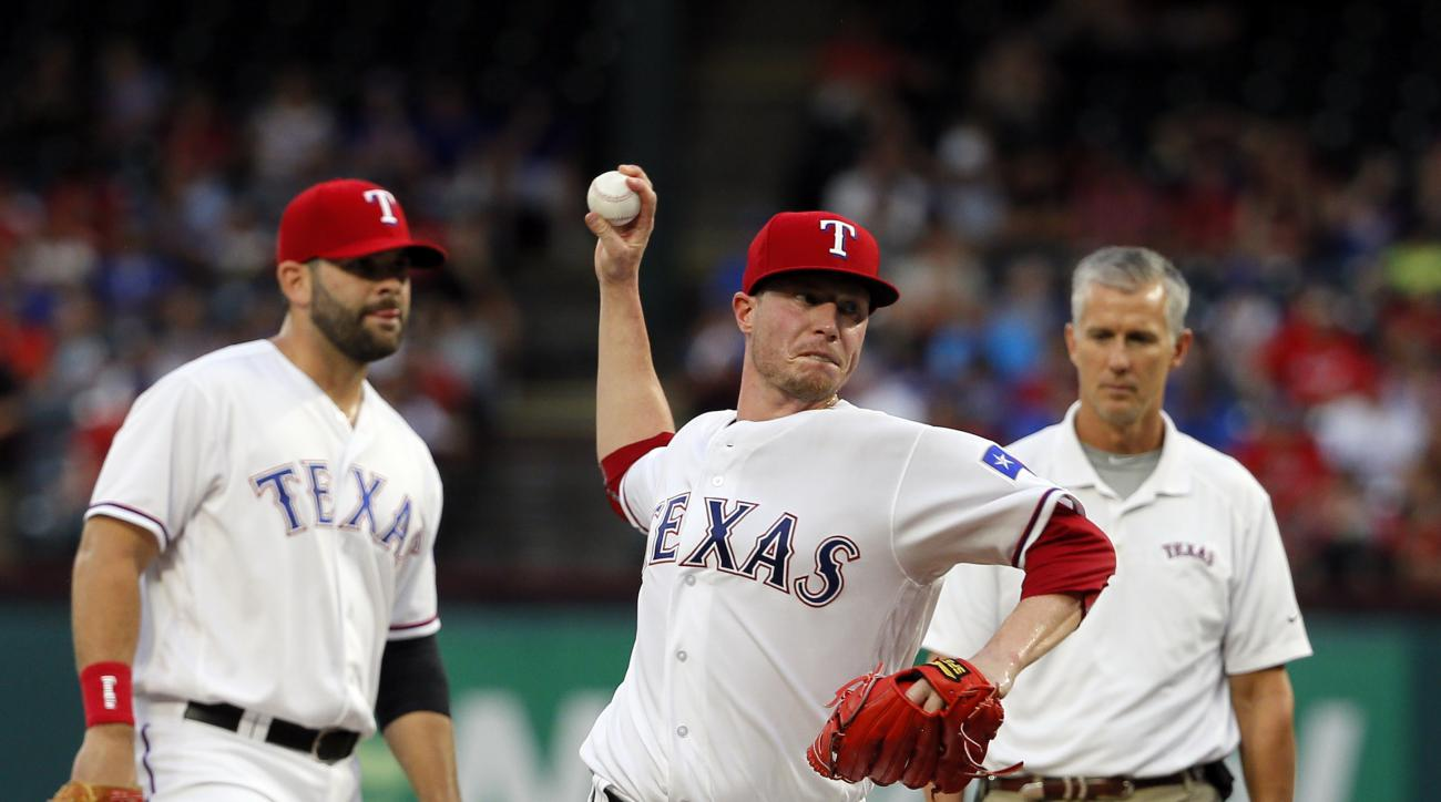 Texas Rangers starting pitcher Lucas Harrell throws as first baseman Mitch Moreland and athletic trainer Kevin Harmon, right rear, watch in the second inning of a baseball game against the Oakland Athletics on Tuesday, Aug. 16, 2016, in Arlington, Texas.