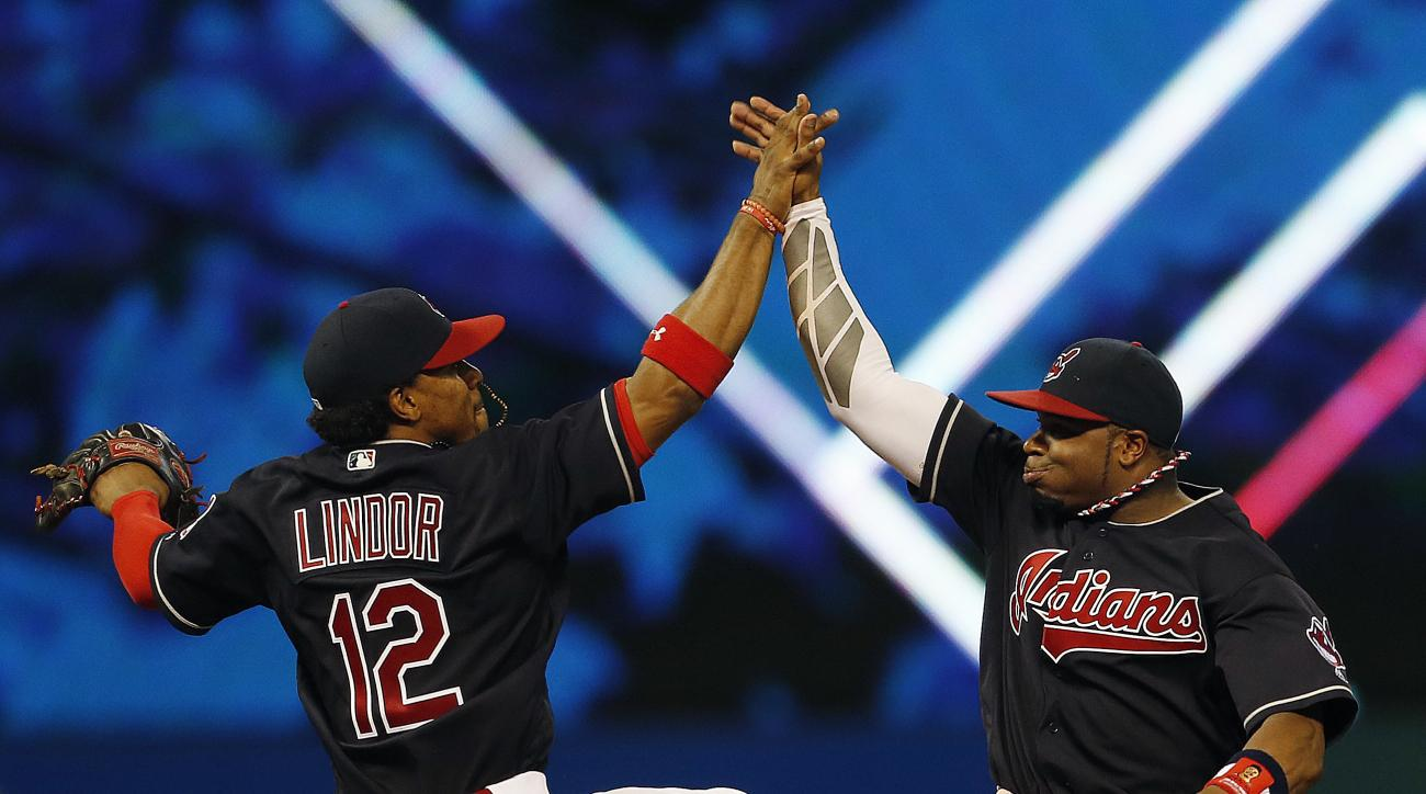 Cleveland Indians' Francisco Lindor (12) and Rajai Davis (20) celebrate the team's 3-1 win over the Chicago White Sox in a baseball game Tuesday, Aug. 16, 2016, in Cleveland. (AP Photo/Ron Schwane)