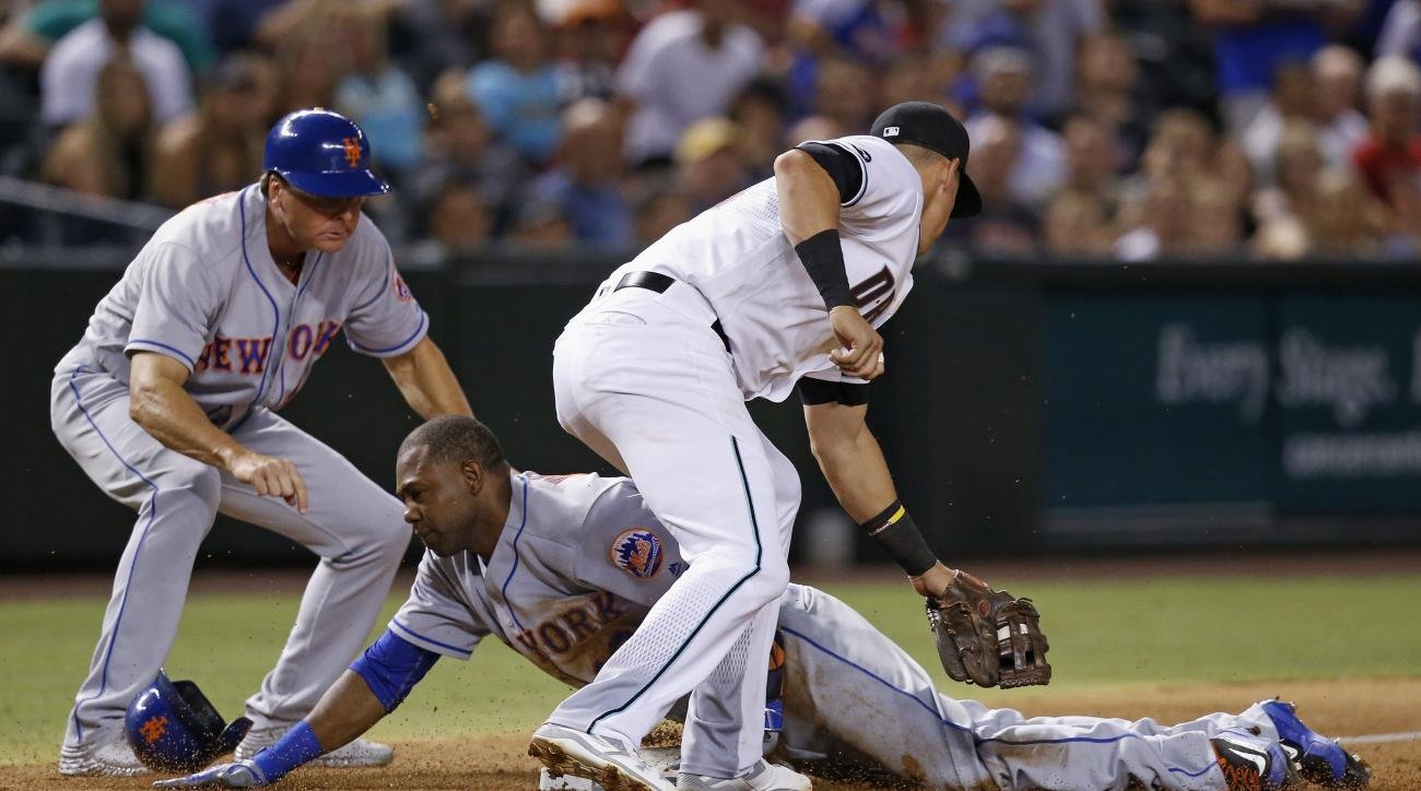New York Mets' Alejandro De Aza slides safely into third base as Arizona Diamondbacks' Jake Lamb, right, applies a late tag as Mets third base coach Tim Teufel watches during the sixth inning of a baseball game Tuesday, Aug. 16, 2016, in Phoenix. De Aza h