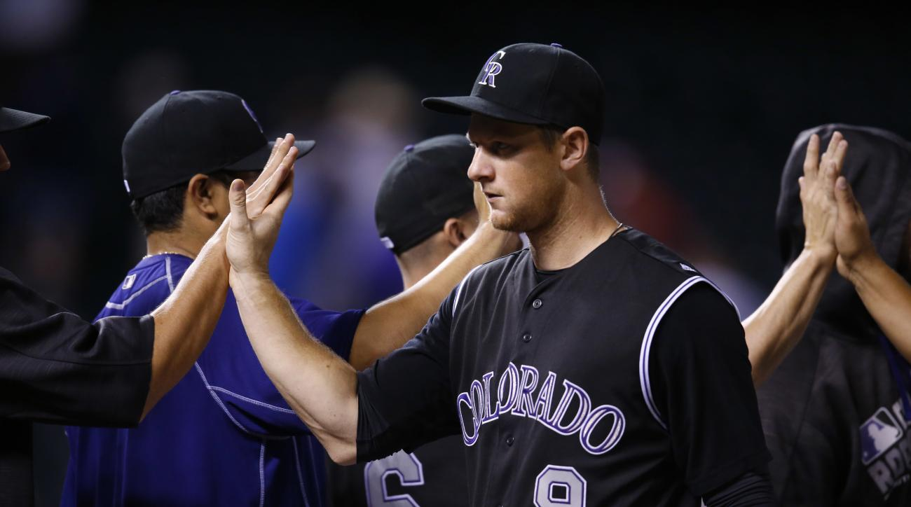 Colorado Rockies' DJ LeMahieu is congratulated by teammates after helping to retire the Washington Nationals in the ninth inning of a baseball game Tuesday, Aug. 16, 2016 in Denver. Colorado won 6-2. (AP Photo/David Zalubowski)