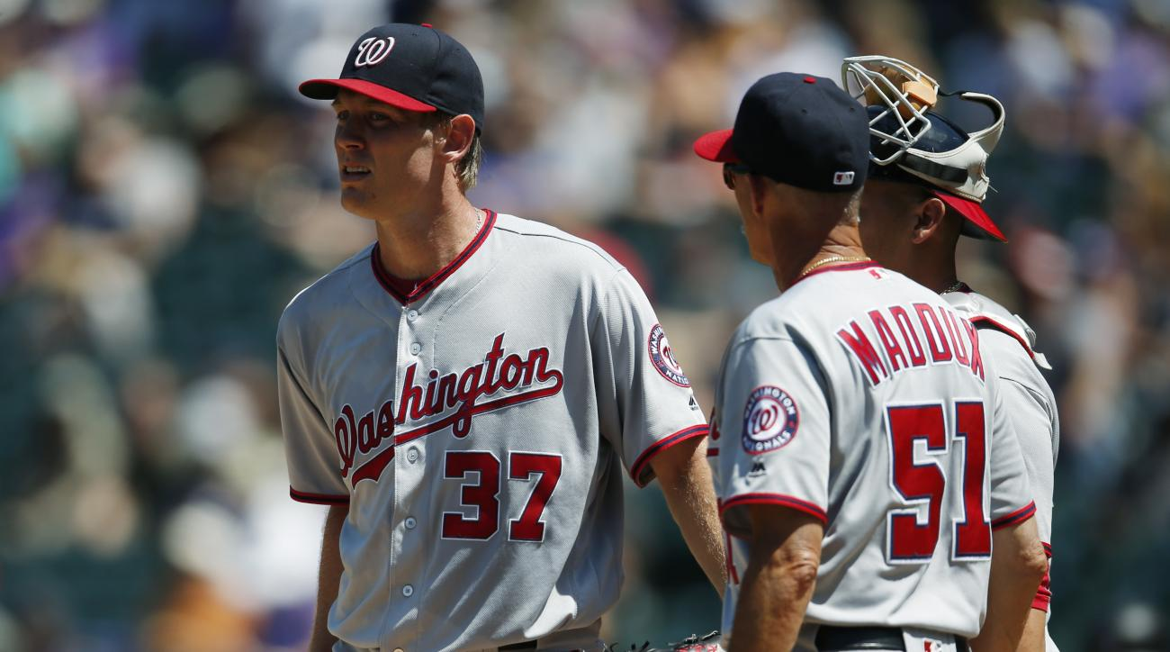 Washington Nationals starting pitcher Stephen Strasburg, left, confers with pitching coach Mike Maddux, center, and catcher Wilson Ramos after Strasburg gave up an RBI-single to Colorado Rockies' Nolan Arenado in the first inning of a baseball game Wednes