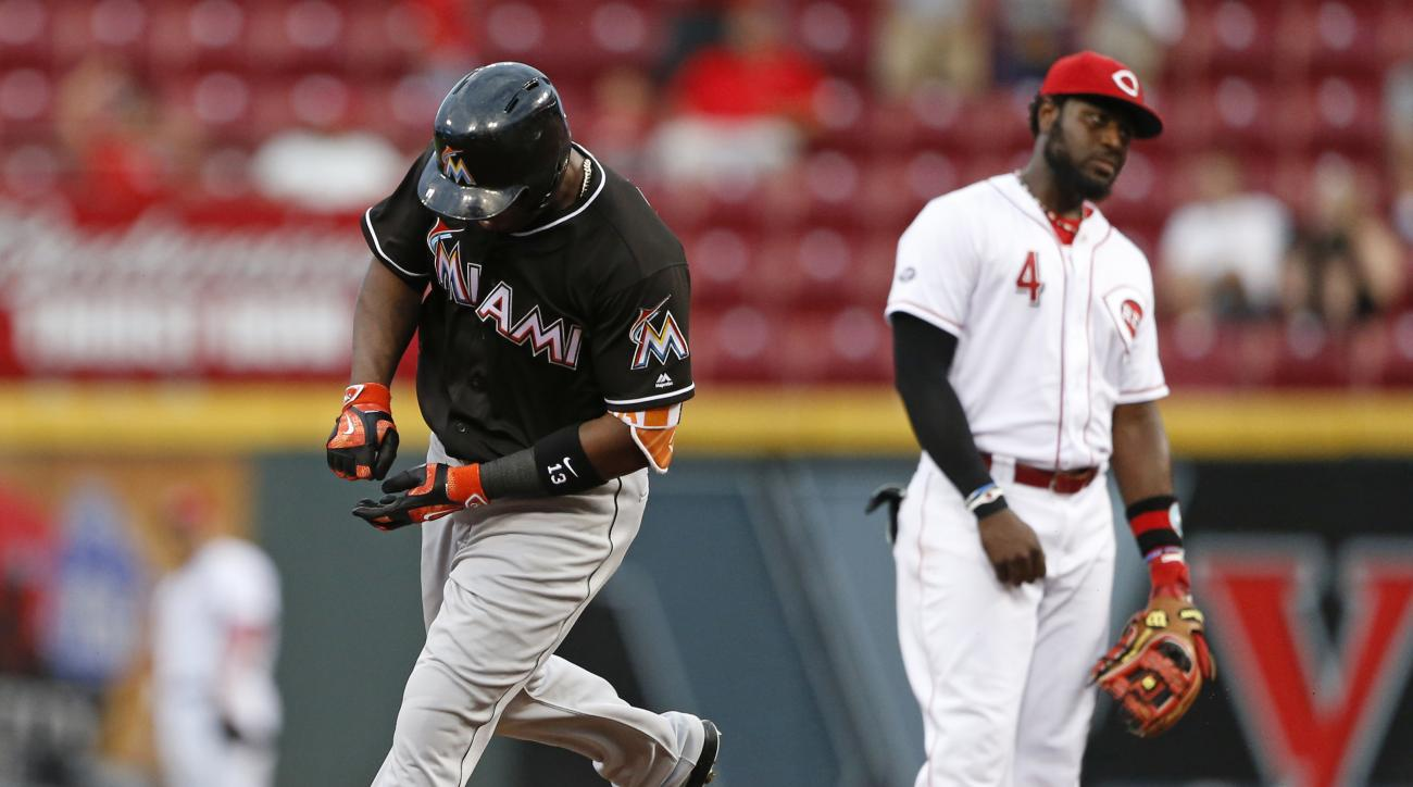 Miami Marlins' Marcell Ozuna, left, rounds second base on a solo home run as Cincinnati Reds second baseman Brandon Phillips reacts during the fourth inning of a baseball game, Wednesday, Aug. 17, 2016, in Cincinnati. (AP Photo/Gary Landers)