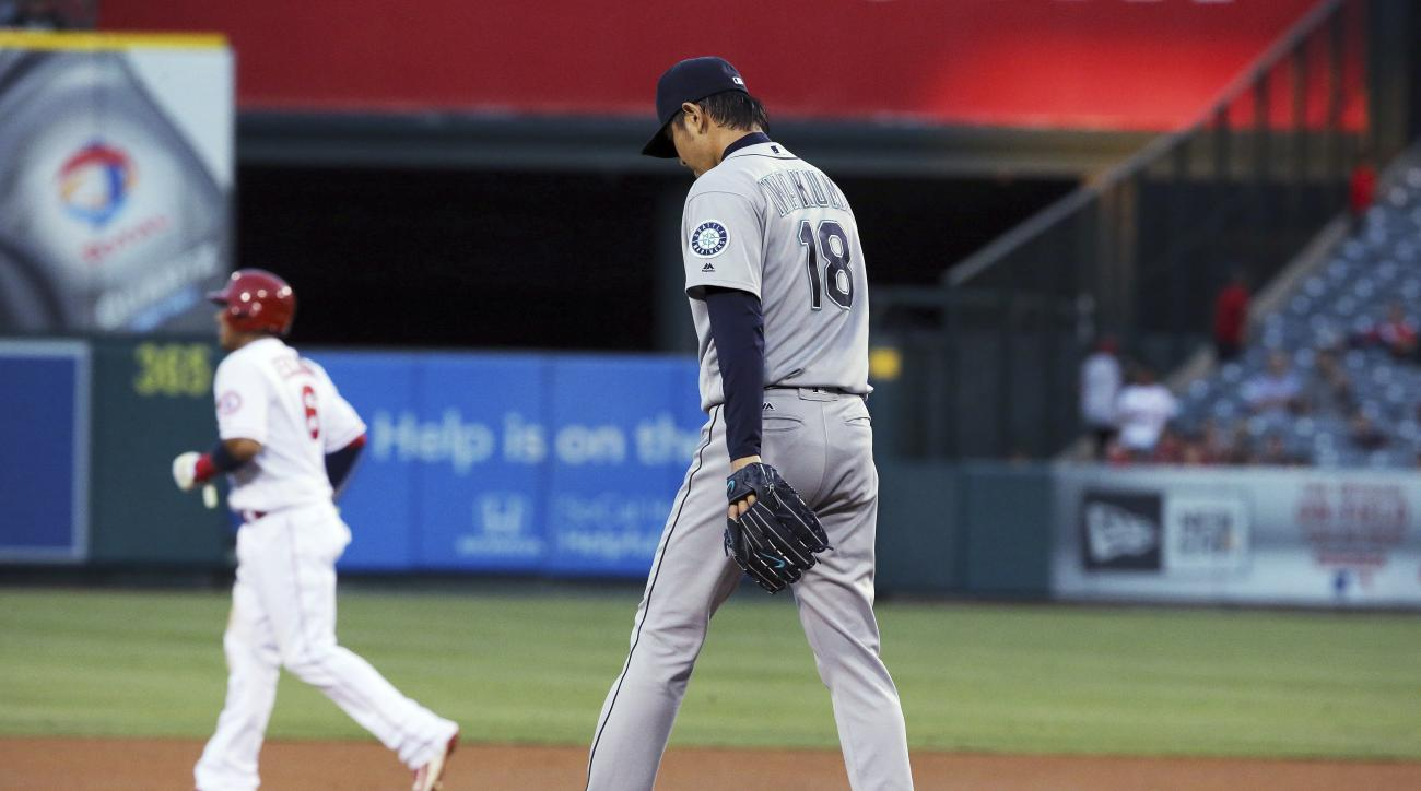 Seattle Mariners pitcher Hisashi Iwakuma, of japan, returns to the mound after walking Los Angeles Angels' Mike Trout, advancing Yunel Escobar to second, background, during the first inning of a baseball game in Anaheim, Calif., Thursday, Aug. 18, 2016. (