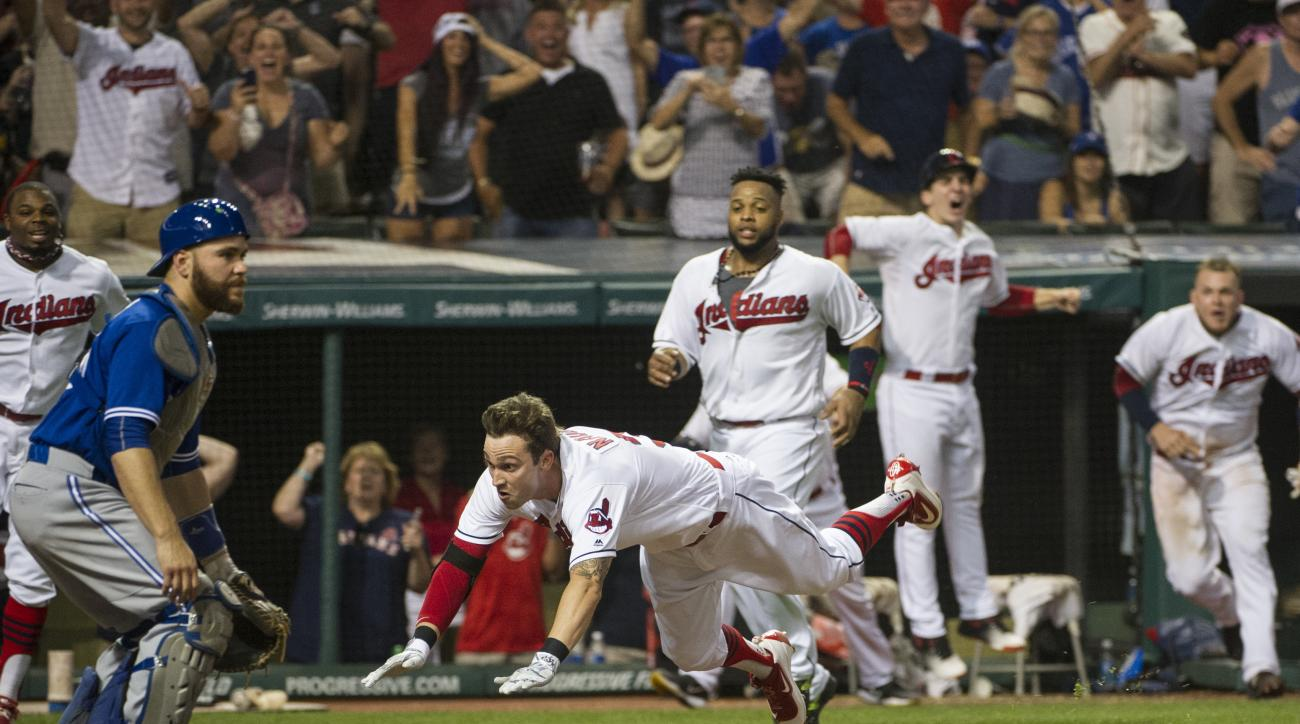 Cleveland Indians' Tyler Naquin, dives for home plate for an inside-the-park home run off Toronto Blue Jays relief pitcher Roberto Osnuo, for the game-winning run in a baseball game in Cleveland, Friday, Aug. 19, 2016. Blue Jays catcher Russell Martin wai