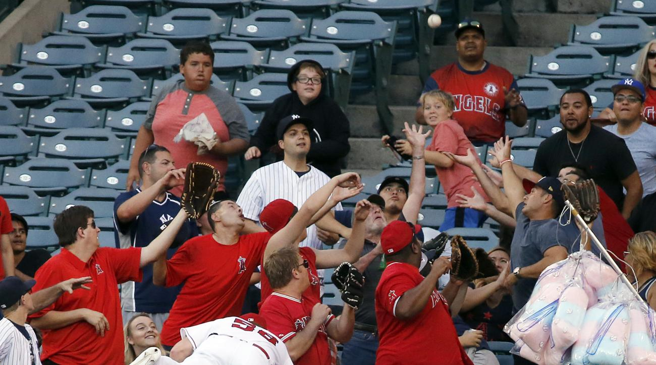 Los Angeles Angels right fielder Kole Calhoun tumbles over the wall, unable to reach a solo home run by New York Yankees' Jacoby Ellsbury during the first inning of a baseball game in Anaheim, Calif., Friday, Aug. 19, 2016. (AP Photo/Reed Saxon)