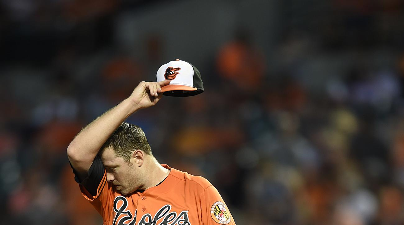 Baltimore Orioles starting pitcher Chris Tillman wipes his face after issuing a walk to load the bases in the third inning of a baseball game against the Houston Astros, Saturday, Aug. 20, 2016, in Baltimore. (AP Photo/Gail Burton)