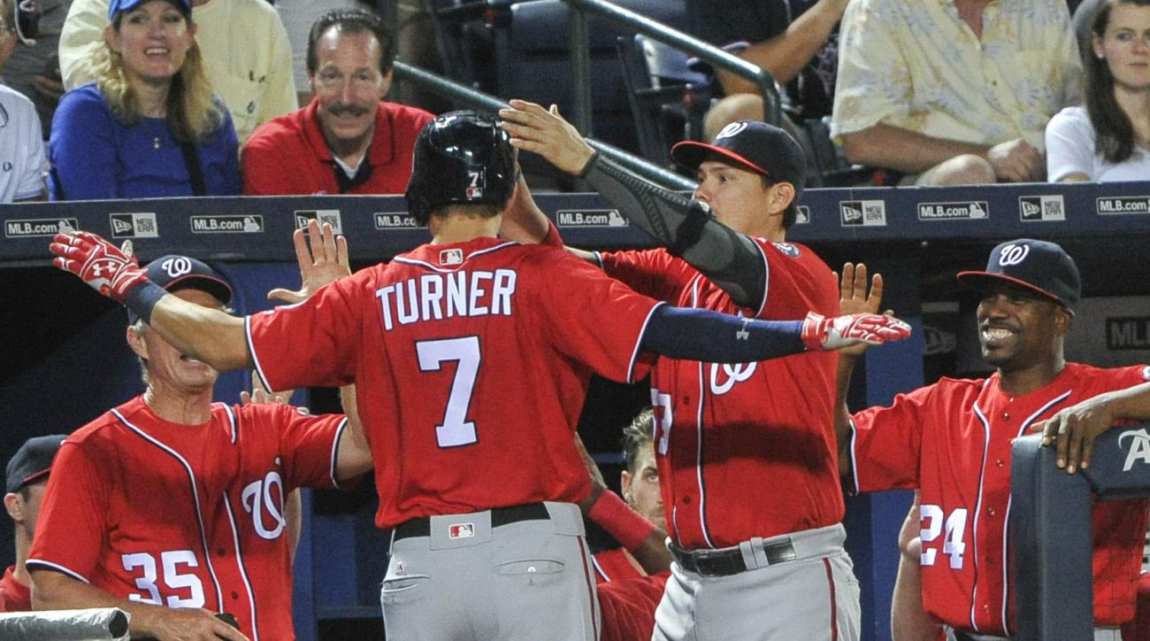 Washington Nationals' Trea Turner (7) is welcomed into the dugout after hitting a three run home run against the Atlanta Braves during the fourth inning of a baseball game, Saturday, Aug. 20, 2016, in Atlanta. (AP Photo/John Amis)