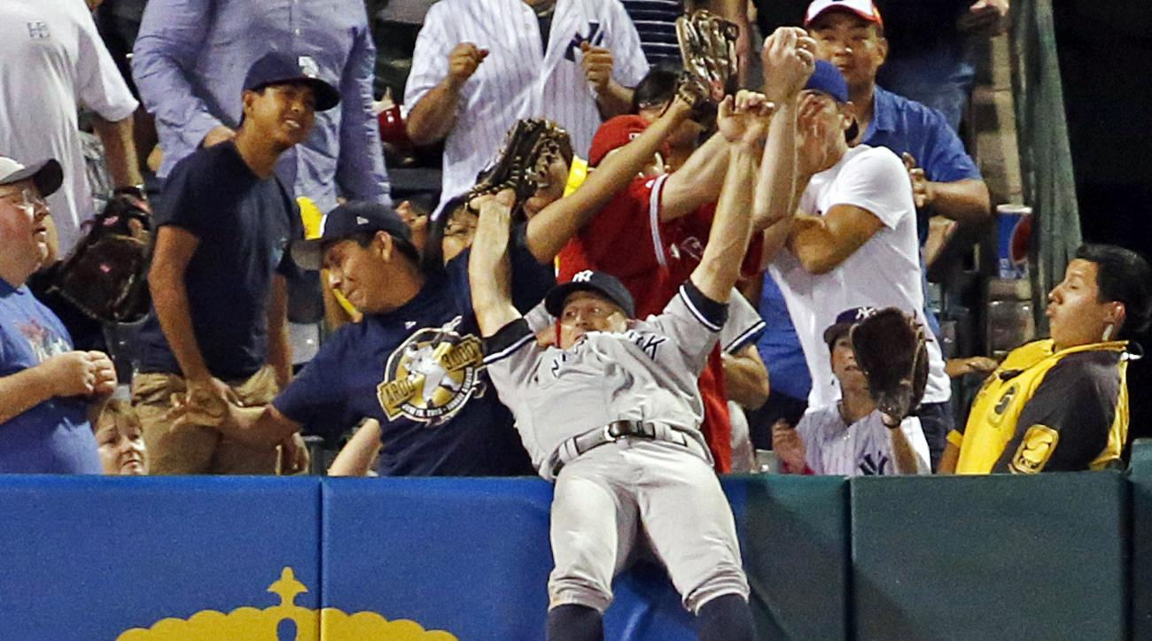 New York Yankees left fielder Brett Gardner falls backward over the wall after catching long fly ball off the Los Angeles Angels' J.J. Cron in the seventh inning of a baseball game in Anaheim, Calif., Saturday, Aug. 20, 2016. (AP Photo/Reed Saxon)