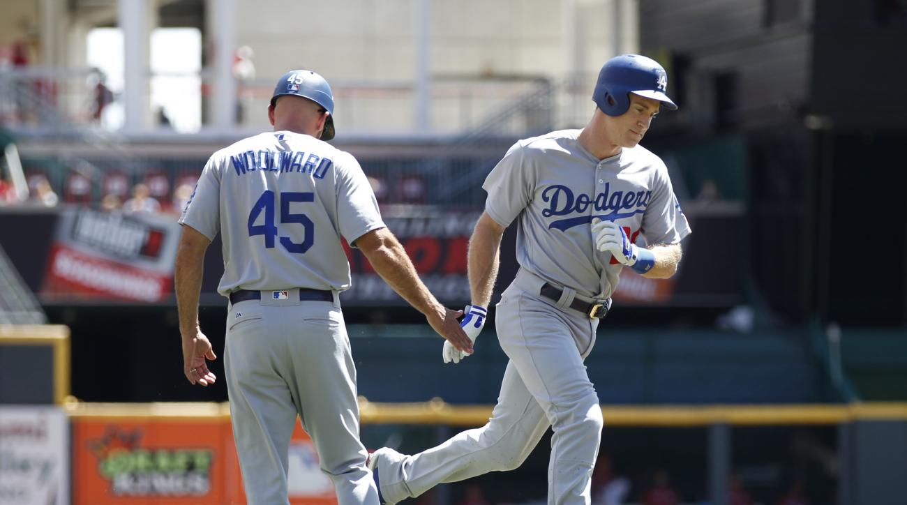 Los Angeles Dodgers' Chase Utley (26) is congratulated by third base coach Chris Woodward (45) as he rounds the bases with a solo home run off Cincinnati Reds starting pitcher Anthony DeSclafani during the first inning of a baseball game, Sunday, Aug. 21,