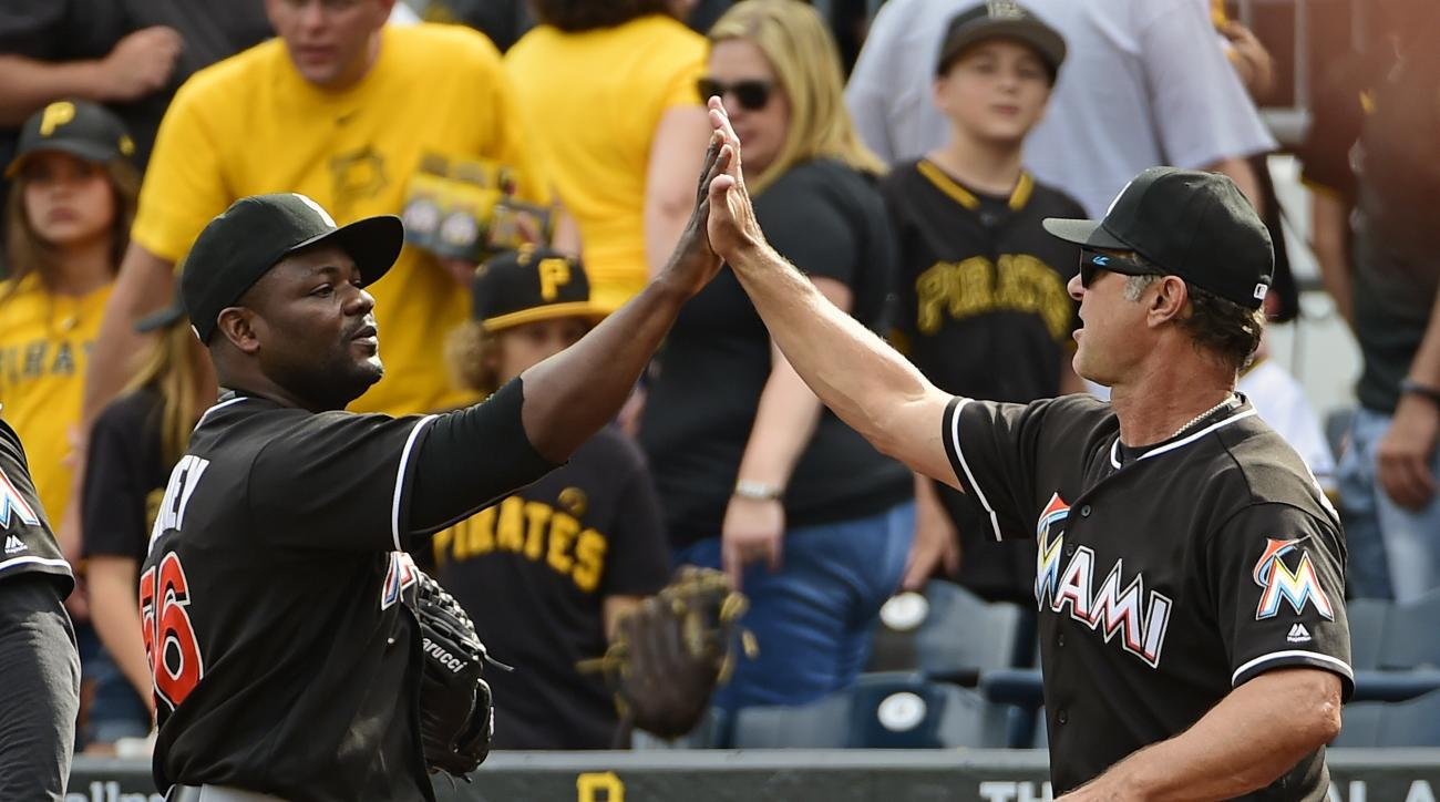 Miami Marlins' Fernando Rodney, left, high-fives manager Don Mattingly after they defeated the Pittsburgh Pirates in a baseball game in Pittsburgh, Sunday, Aug. 21, 2016. (AP Photo/Fred Vuich)