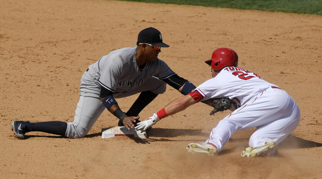 Los Angeles Angels' Mike Trout, right, is tagged out by New York Yankees second baseman Starlin Castro as he tries to steal second during the eighth inning of a baseball game, Sunday, Aug. 21, 2016, in Anaheim, Calif. The Angels won 2-0. (AP Photo/Mark J.