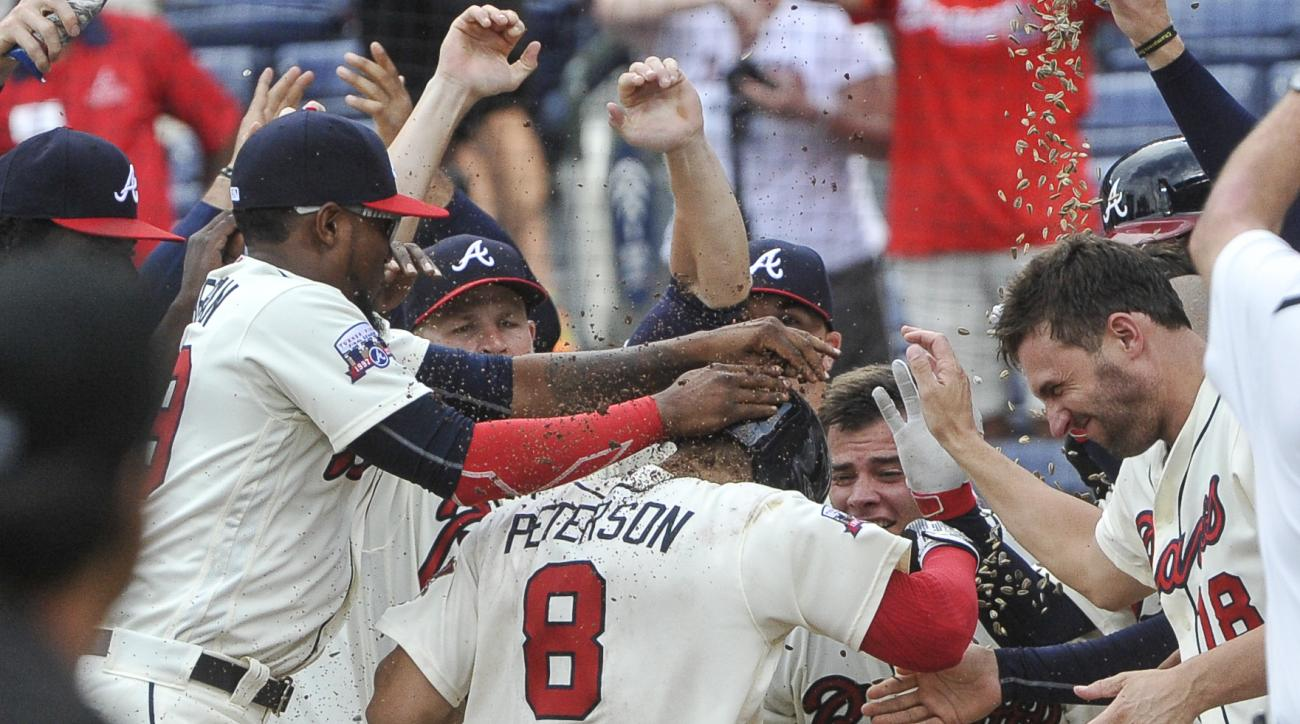 Atlanta Braves' Jace Peterson (8) is welcomed at home plate by celebrating teammates after hitting a walkoff home run against the Washington Nationals during the tenth inning of a baseball game, Sunday, Aug. 21, 2016, in Atlanta. (AP Photo/John Amis)