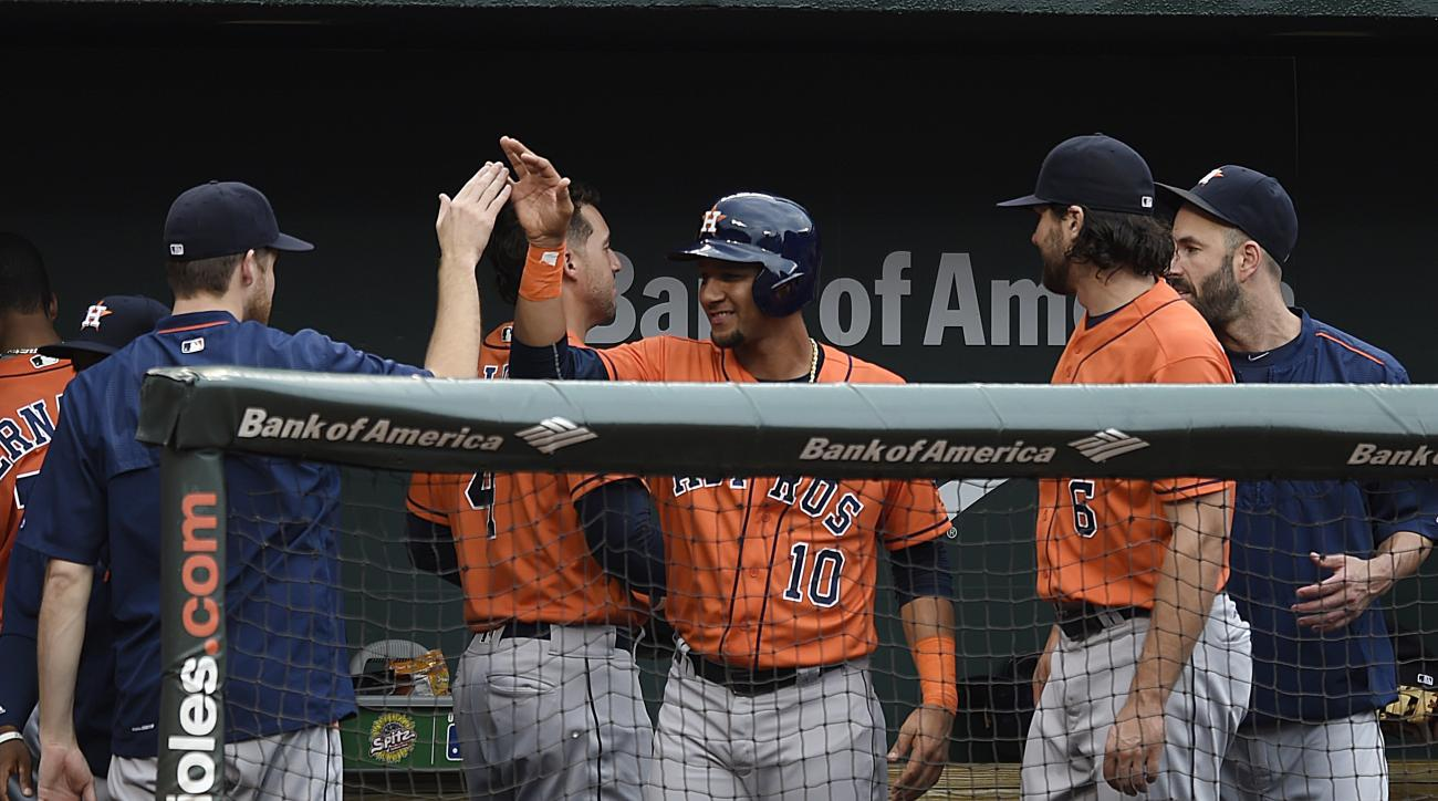 Houston Astros' Yulieski Gurriel, center, is congratulated by his team in the second inning of a baseball game after hitting a single in his major league debut against the Baltimore Orioles, Sunday, Aug. 21, 2016, in Baltimore. (AP Photo/Gail Burton)