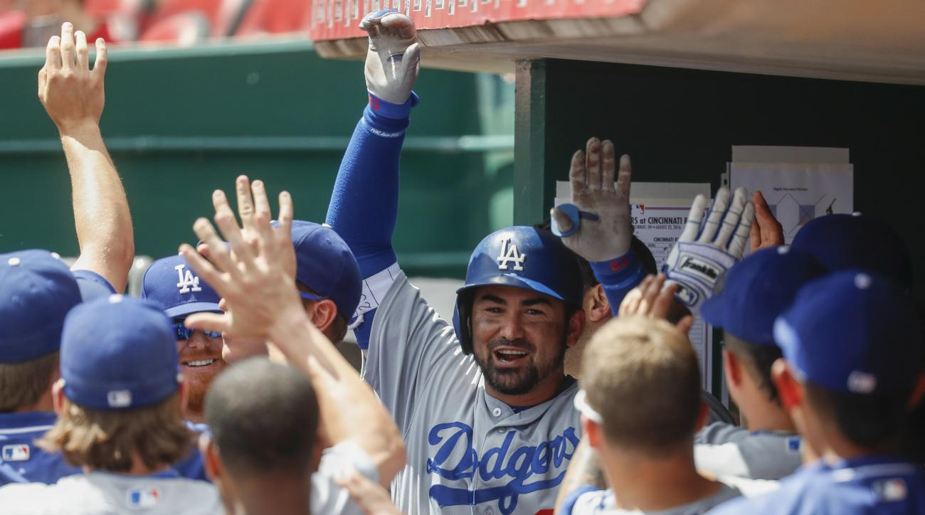 Los Angeles Dodgers' Adrian Gonzalez, center, celebrates in the dugout after hitting a solo home run off Cincinnati Reds relief pitcher Jumbo Diaz in the fifth inning of a baseball game, Monday, Aug. 22, 2016, in Cincinnati. (AP Photo/John Minchillo)