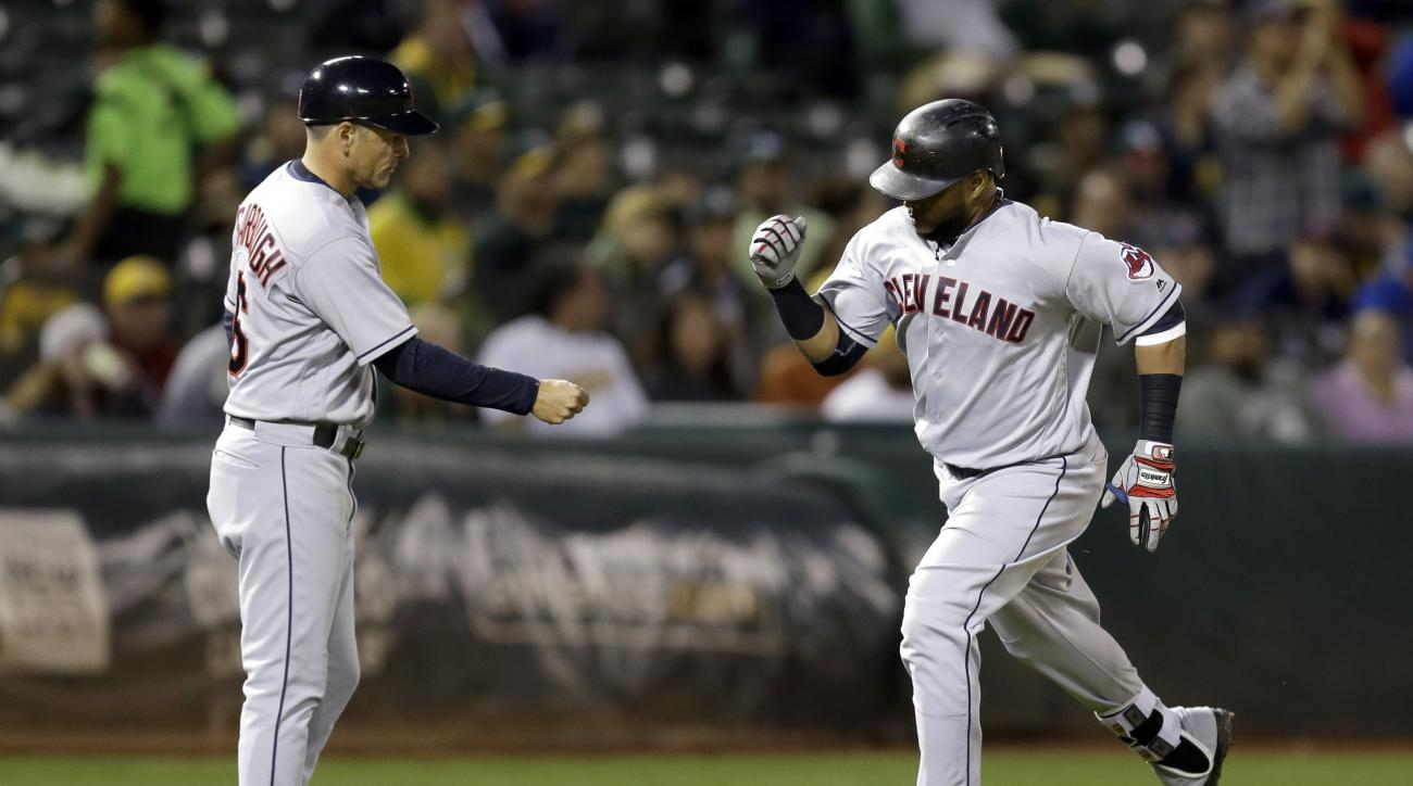 Cleveland Indians' Carlos Santana, right, celebrates with third base coach Mike Sarbaugh after hitting a home run off Oakland Athletics' Ryan Dull in the eighth inning of a baseball game Monday, Aug. 22, 2016, in Oakland, Calif. (AP Photo/Ben Margot)