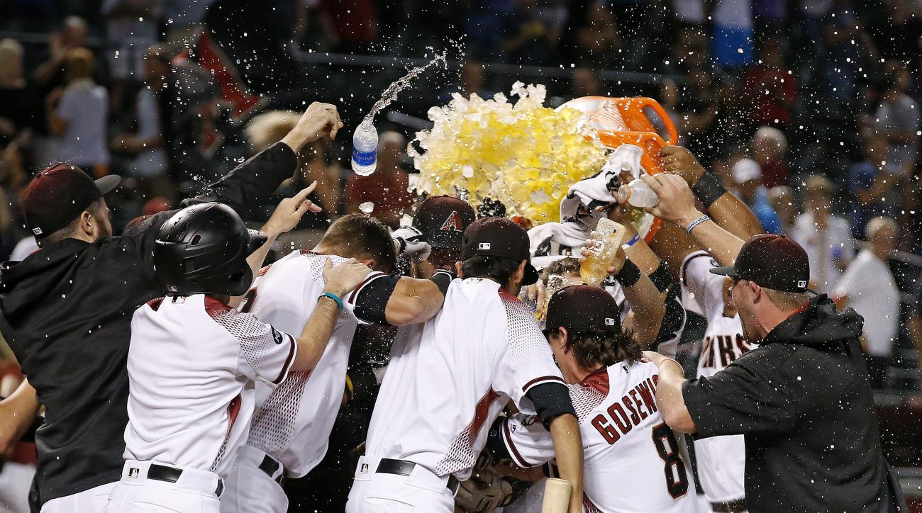 Arizona Diamondbacks players surround Paul Goldschmidt after his walk off home run against the Atlanta Braves during the ninth inning of a baseball game Monday, Aug. 22, 2016, in Phoenix. The Diamondbacks defeated the Braves 9-8. (AP Photo/Ross D. Frankli