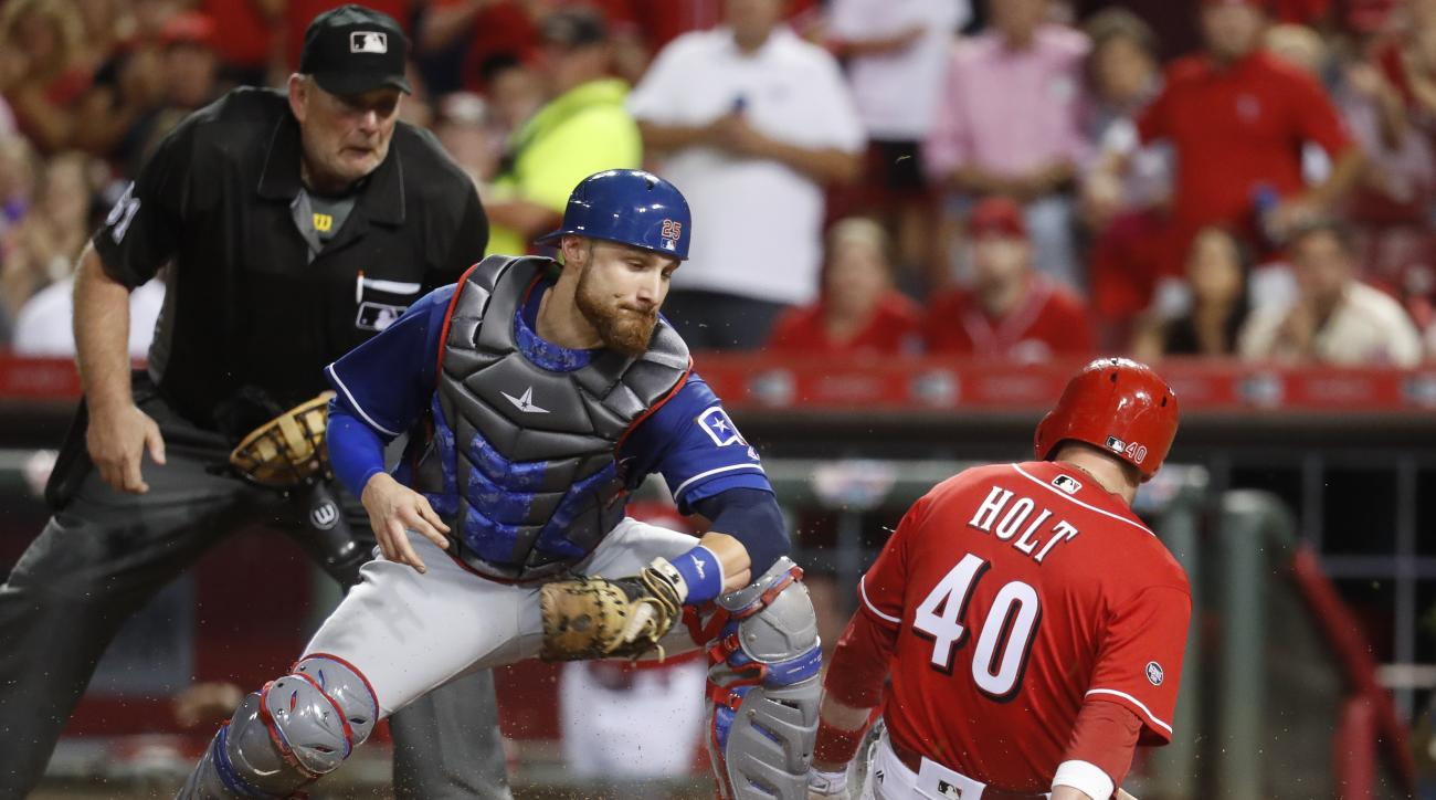 Cincinnati Reds' Tyler Holt (40) scores against Texas Rangers catcher Jonathan Lucroy during the sixth inning of a baseball game, Tuesday, Aug. 23, 2016, in Cincinnati. (AP Photo/John Minchillo)