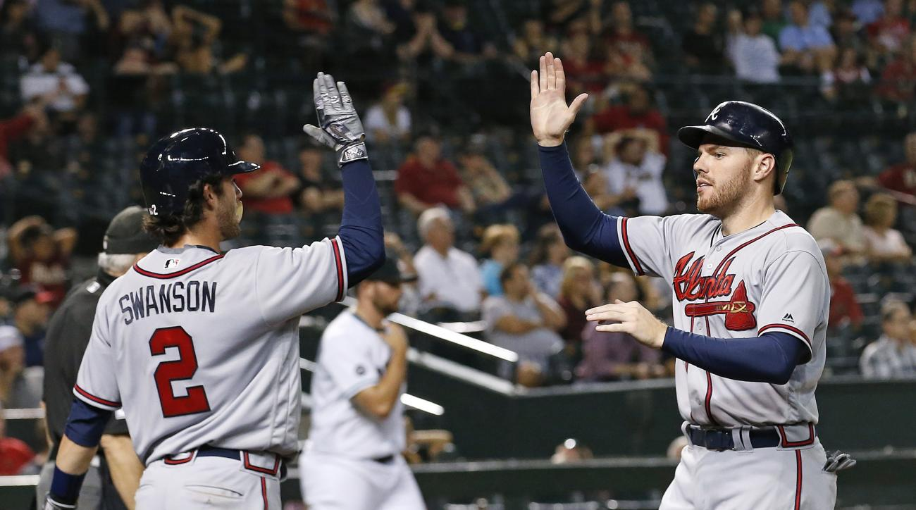 Atlanta Braves' Freddie Freeman, right, and Dansby Swanson (2) celebrate as both scored against the Arizona Diamondbacks during the eighth inning of a baseball game Tuesday, Aug. 23, 2016, in Phoenix. (AP Photo/Ross D. Franklin)