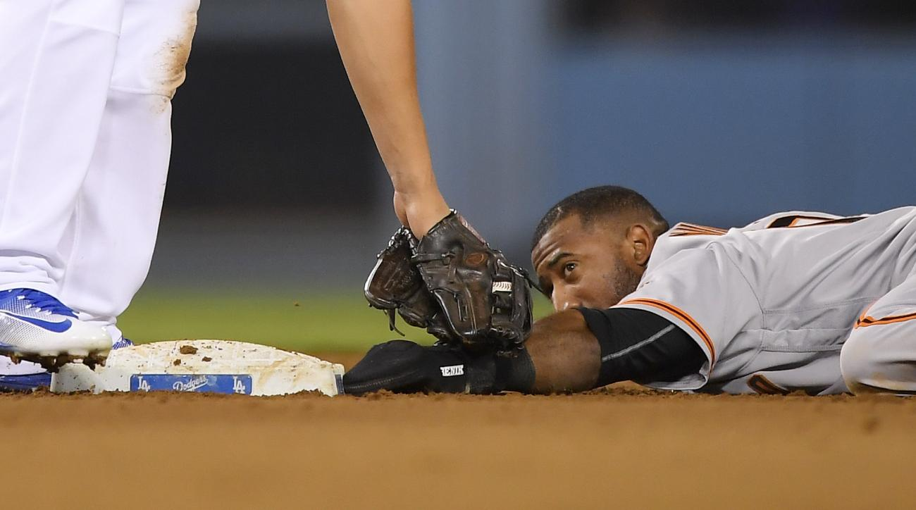 San Francisco Giants' Eduardo Nunez, right, lies on the ground after stealing second as Los Angeles Dodgers shortstop Corey Seager puts a late tag on him during the sixth inning of a baseball game, Tuesday, Aug. 23, 2016, in Los Angeles. (AP Photo/Mark J.