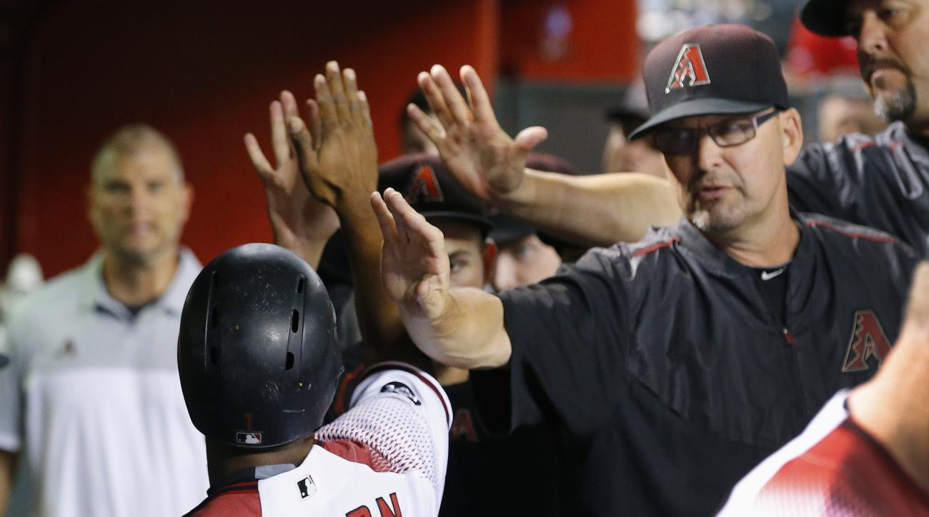 Arizona Diamondbacks' Michael Bourn, left, gets high-fives from teammates and coaches, including assistant hitting coach Mark Grace, right, after Bourn scored a run against the Atlanta Braves during the first inning of a baseball game Wednesday, Aug. 24,