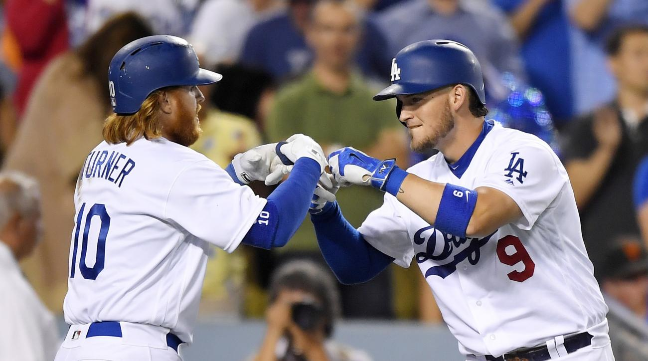 Los Angeles Dodgers' Justin Turner, left, celebrates his solo home run with Yasmani Grandal during the fourth inning of a baseball game Wednesday, Aug. 24, 2016, in Los Angeles. (AP Photo/Mark J. Terrill)
